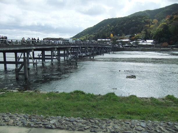 清流をまたいで渡月橋の架かる景色